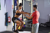 Trainer assisting client, doing box jumps - JSMF00504