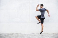 Athlete jumping in front of white wall - JSMF00513