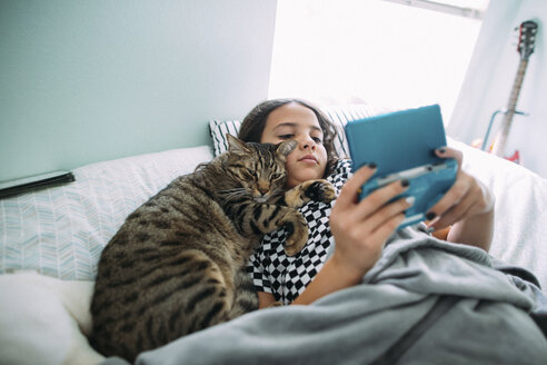 High angle view of girl playing video game while lying with cat on bed at home - CAVF50592