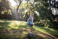 Portrait of girl with backpack standing on tree stump in forest - CAVF50595