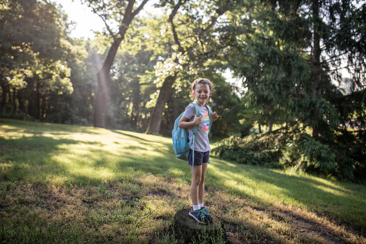 Portrait of girl with backpack standing on tree stump in forest - CAVF50595 - Cavan Images/Westend61