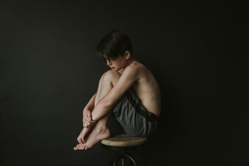 Side view of sad shirtless boy sitting on stool against black background - CAVF50607