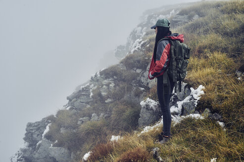 Side view of female hiker standing on Balkan Mountains during foggy weather - CAVF50640