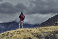 Male hiker photographing while standing on mountain against cloudy sky - CAVF50643