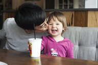 Father kissing happy daughter while sitting at table in cafe - CAVF50655