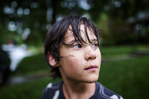 Close-up of thoughtful boy with dirty face standing at yard during rainy season - CAVF50658