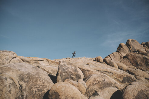 Mid distance view of boy running on rock formations against sky at desert - CAVF50691