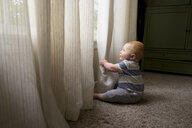 Side view of baby boy playing with curtains while sitting on carpet at home - CAVF50730
