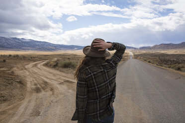 Rear view of woman wearing hat while standing on road against cloudy sky at Bryce Canyon National Park - CAVF50742