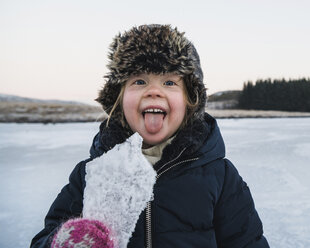 Portrait of playful girl sticking out tongue while holding ice during winter - CAVF50748