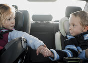 Siblings holding hands while sitting in car - CAVF50757
