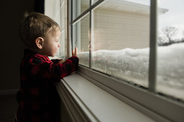 Side view of boy looking through window while standing at home during winter - CAVF50766