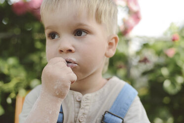 Close-up of thoughtful boy looking away in yard - CAVF50820