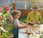 Brothers kneading dough on table in yard - CAVF50823