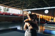Happy friends embracing while standing at gym - CAVF50853