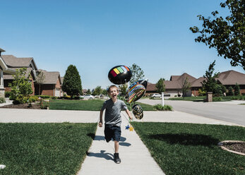 Happy boy with balloons running on footpath against clear blue sky during sunny day - CAVF50865