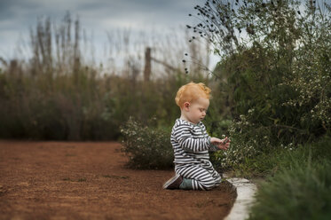 Side view of baby boy holding stick while kneeling at park - CAVF50874