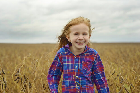 Portrait of cheerful girl standing amidst soybean's field against sky - CAVF50901