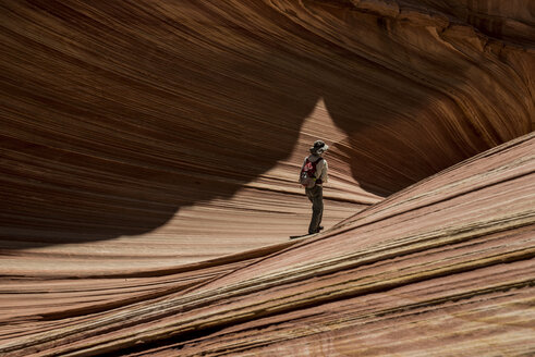 Hiker with backpack standing on Marble Canyon during sunny day - CAVF50934