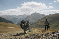 Rear view of biker standing by motorbike on mountain against cloudy sky - CAVF50955
