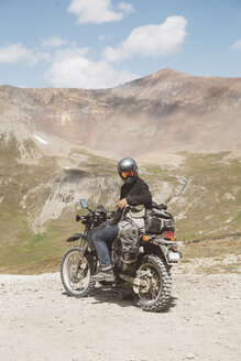 Biker with motorbike sitting on mountain against sky during sunny day - CAVF50958