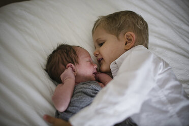 High angle view of boy lying by newborn brother on bed at home - CAVF50982