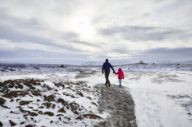 Rear view of father and daughter holding hands while walking on snow covered landscape against cloudy sky - CAVF51006