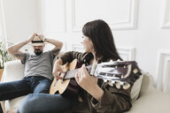 Relaxed couple sitting on couch, woman playing the guitar at home - KMKF00606