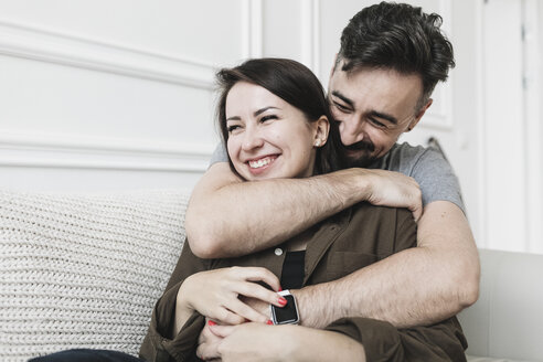 Happy couple embracing at home - KMKF00609
