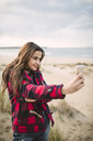 Portrait of smiling young woman taking selfie with smartphone on the beach - RAEF02186