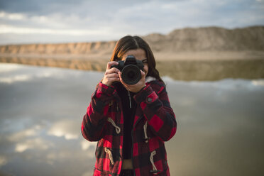 Young woman taking picture with camera on the beach - RAEF02189