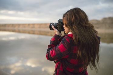 Young woman taking picture with camera on the beach - RAEF02192