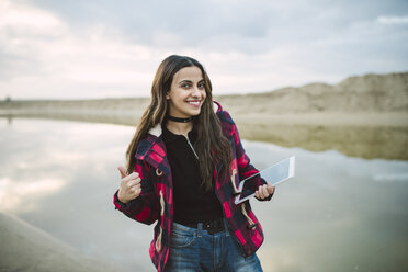 Portrait of smiling young woman taking selfie with smartphone on the beach - RAEF02195