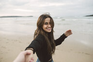 Portrait of smiling young woman holding hands on the beach - RAEF02198