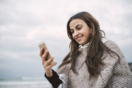 Portrait of smiling young woman looking at cell phone - RAEF02204