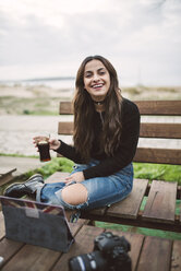 Portrait of laughing young woman with camera and tablet sitting on bench outdoors - RAEF02210