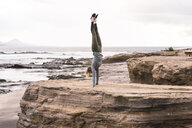 Full length of woman practicing handstand on rock at beach - CAVF51089