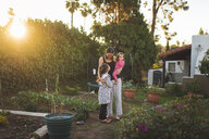 Mother with daughters standing in yard against sky during sunset - CAVF51098