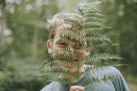 Close-up portrait of cheerful boy holding fern against face - CAVF51125