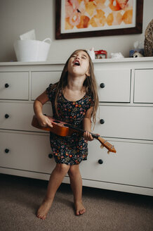 Full length of girl playing guitar while standing at home - CAVF51128