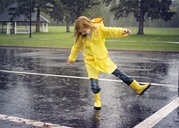 Playful girl wearing raincoat while dancing on road during rainfall - CAVF51143