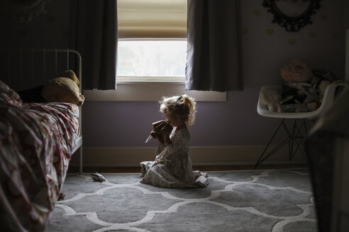 Side view of girl playing while sitting on carpet against window in bedroom - CAVF51152