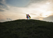 Low angle view of playful girl holding multi colored textile while running on hill against cloudy sky - CAVF51213