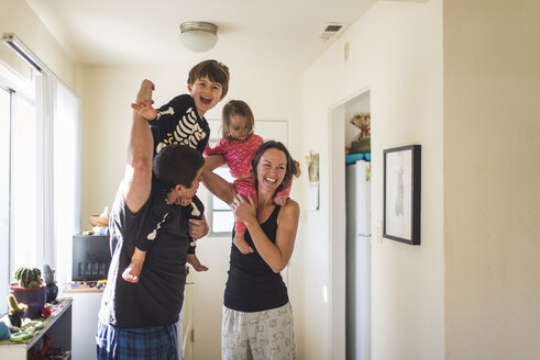 Happy parents carrying children on shoulders while standing at home - CAVF51231