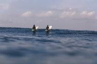 Rear view of friends surfing on sea against sky - CAVF51240