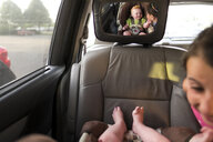 Reflection of sister playing with brother seen in back seat mirror - CAVF51246