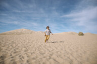Playful boy running against cloudy sky at desert during sunny day - CAVF51291