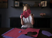 Girl cutting craft papers in heart shape on table at home - CAVF51324