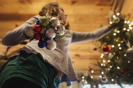Low angle view of girl decorating Christmas Tree at home - CAVF51342