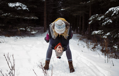 Happy mother playing with daughter while standing in forest during winter - CAVF51360